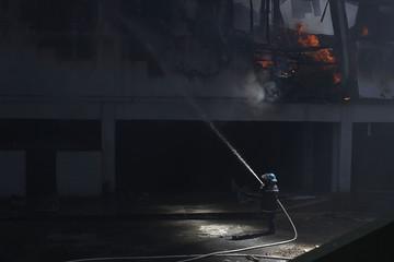 Salvadoran firefighter sprays water at a Las Cascadas shopping mall after a fire broke out inside, in Antiguo Cuscatlan