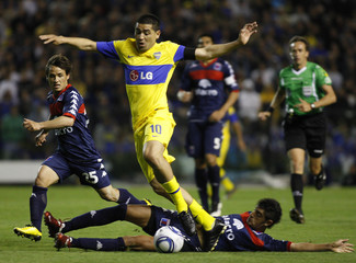 Boca Juniors' Riquelme fights for the ball with Tigre's Martinez during their Argentine First Division soccer match in Buenos Aires
