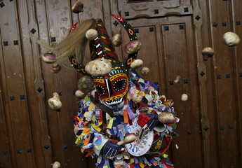 Revellers throw turnips at the Jarramplas, a character who wears a devil-like mask and a colourful costume, as he makes his way through the streets while beating his drum during the Jarramplas traditional festival in Piornal