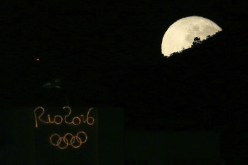 The moon sets behind a building with an Olympics sign in Rio de Janeiro