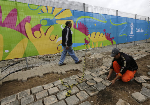 A construction worker continues the installation of pavers outside the Arena Baixada soccer stadium in Curitiba