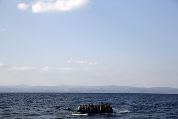 Afghan migrants on a dinghy approach a beach on the island of Lesbos