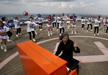 German musician Aaron plays the piano as cheerleaders perform next to him on top of the Yokohama Landmark Tower in Yokohama