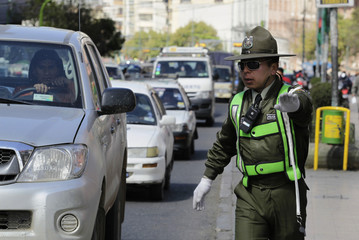 A Bolivian police officer, wearing the new wide brimmed hats as part of a new measure to lower the risk of skin disorders, controls vehicle traffic in La Paz