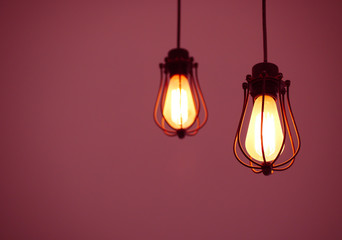 Illuminated hanging light bulbs on pink plain background with free text space
