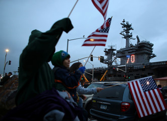 Kids wave American flags as friends and family watch the USS Carl Vinson aircraft carrier depart on deployment from Naval Station North Island in Coronado, California