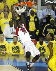 Louisville Harrell dunks next to Michigan Robinson III in the first half of their NCAA men's Final Four championship basketball game in Atlanta
