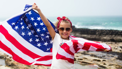 American flag. Little smiling patriotic girl holding an American flag flying in the wind on the ocean beach. National holiday July 4th, Independence day USA