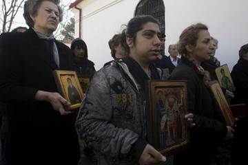Christian Orthodox Iranian migrants Roya and Sami, who have been living for twenty days at a makeshift camp for refugees and migrants, hold icons during a mass marking the Sunday of Orthodoxy at the church of the village of Idomeni