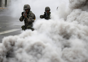 South Korean soldiers walk through smoke as they take part in an anti-terror and security drill at the Integrated Government Complex in Sejong