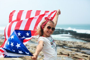 American flag. Little smiling  patriotic girl with long blond hair, red head band  bandana and sunglasses holding an american flag waving in the wind on the ocean beach. National 4 july. Memorial day