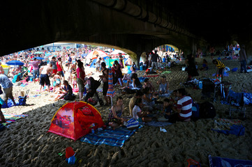 People shelter under the pier on Bournemouth beach, in Bournemouth, southern England