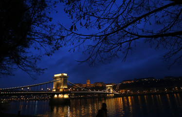 The iconic Chain Bridge of Budapest spans the Danube river and the Royal Palace is seen in the background