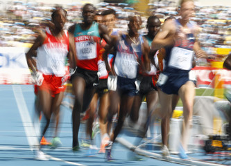 Competitors run through a turn in their men's 5,000 metres heat at the IAAF World Championships in Daegu