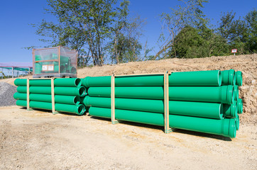 pallets of green sewer pipes at construction site
