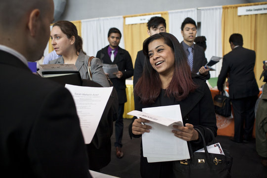 A college senior meets with a company spokesperson at a job fair in New York
