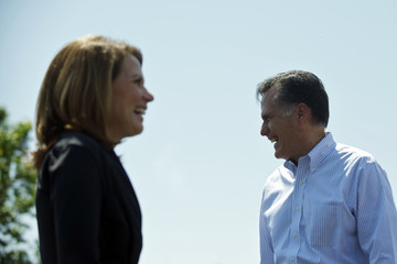 Mitt Romney and Michele Bachmann laugh during a speech by Bob McDonnell during a rally at Crofton Industries in Portsmouth