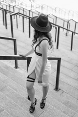 Young beautiful sexy woman wearing trendy outfit, white dress, black hat and leather swordbelt. Longhaired brunette posing in the city street. Outdoor fashion photography