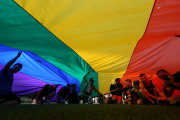 People sit under a giant rainbow flag during a vigil for the Pulse night club victims following last weeks shooting in Orlando