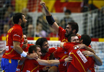 Spain's players celebrate winning their Men's Handball World Championship quarter-final match against Germany in Zaragoza