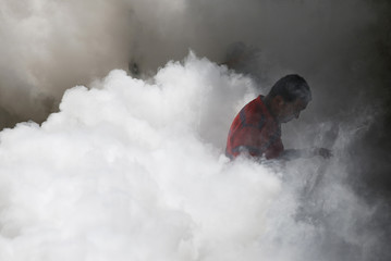 Man stands enveloped in a cloud of smoke as a truck is used to carry out fumigation to help control the spread of Chikungunya and dengue fever, which are caused by viruses carried by mosquitoes, in Caracas
