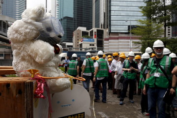 Workers from the Lands Department gather to remove encampments as a teddy bear wearing a mask is displayed by pro-democracy protesters outside the government headquarters in Hong Kong