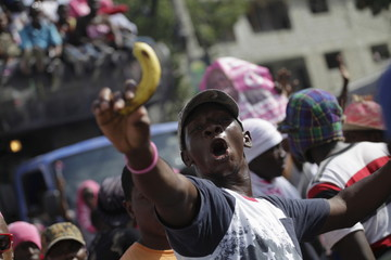 A supporter of presidential candidate Jovenel Moise chants as he holds a banana during a demonstration to demand the speedy organization of a postponed presidential runoff election in Port-au-Prince, Haiti