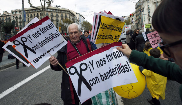 A man hands out flyers before a protest against government austerity measures in central Barcelona