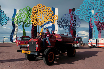 A man poses for pictures on a fire truck during an exhibition of old fire trucks in Managua