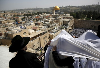 Jewish worshippers covered with prayer shawls stands on the rooftop overlooking the Western Wall during a special priestly blessing for Passover in Jerusalem's Old City
