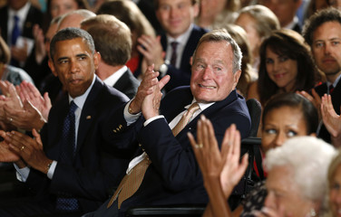 U.S. President Barack Obama and former President George H. W. Bush applaud during an event to honor the winner of the 5,000th Daily Point of Light Award at the White House in Washington