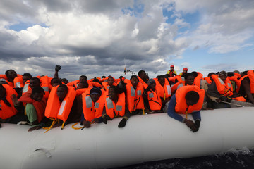Migrants try to reach a rescue craft from their overcrowded raft, as lifeguards from the Spanish NGO Proactiva Open Arms rescue all on aboard
