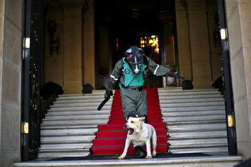 "A protestor wearing a mask and a fake riot police uniform takes part in rally at the ""Club de la Union"" stairs in Santiago"