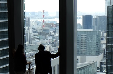 A man and a woman watch outside at the lobby of an office building in Tokyo