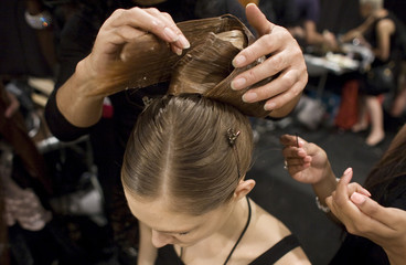 A model has her hair styled backstage before the Zang Toi Spring/Summer 2012 show during New York Fashion Week