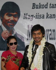 Filipino boxing icon Manny Pacquiao gives a speech beside his wife Jinkee upon his arrival at the Ninoy Aquino International Airport in Manila