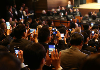 Members of the audience film and photograph China's President Xi Jinping (not pictured) as he attends a meeting of the APEC (Asia-Pacific Economic Cooperation) Ceo Summit in Lima