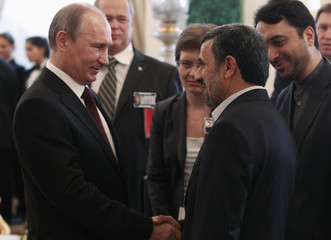 Russia's President Putin talks to his Iranian counterpart Ahmadinejad before the Gas Exporting Countries Forum at the Kremlin in Moscow