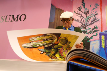 """British artist David Hockney turns pages of his new book """"A Bigger Book"""" during the book fair in Frankfurt"""