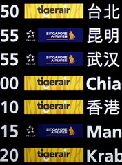 Tiger Airways and Singapore Airlines logos are seen on a flight information screen at Changi Airport in Singapore