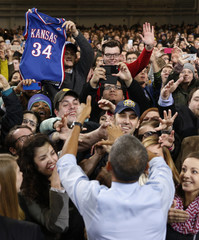A student holds up a basketball uniform as U.S. President Barack Obama shakes hands after speaking during a visit to the University of Kansas in Lawrence
