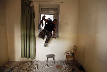 A Free Syrian Army fighter carries his weapon as he jumps from a house's window near Aleppo's historic citadel which is controlled by forces loyal to Syria's President Bashar al-Assad