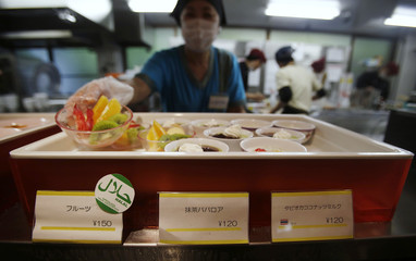 "A staff shows a bowl of cut fruit, above a ""halal certified"" sign, at a dining hall in the Kanda University of International Studies in Chiba"