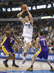 Mavericks forward Nowitzki drives between Lakers forward Odom and guard Farmar before passing during their NBA basketball game in Dallas