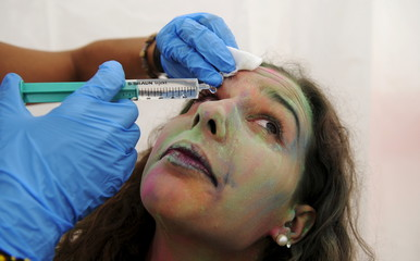 A member of Red Cross cleans the eye of a reveller during the Holi Party Festival at the Niemeyer Center in Aviles