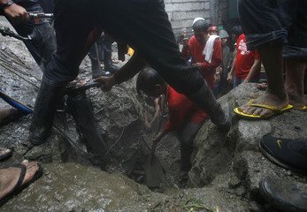 Rescuers search for victims after a wall collapsed on houses amid heavy downpour in Valenzuela City