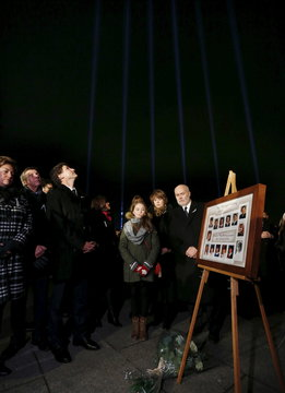 Canadian Prime Minister Justin Trudeau looks up as blue beams of light are projected during a vigil to remember the victims of a mass shooting in Montreal