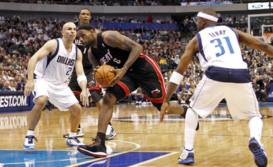 Heat small forward James drives between Mavericks point guard Kidd and shooting guard Terry during their NBA basketball game in Dallas, Texas