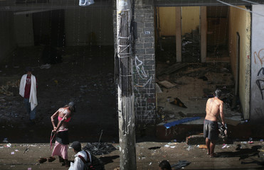 A crack user takes a shower under a drain pipe during a rainstorm in the part of Sao Paulo's Luz neighborhood known as Crackland