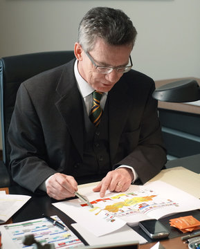 German Defence Minister de Maiziere reads a file showing a map of Afghanistan as he poses after an interview with Reuters in his bureau at the Defence Ministry in Berlin